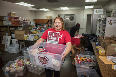 """Isabel Moreno unloads food in the Hungry Wildcat Food Pantry after the food drive, Wildcats Can! culminated with a """"can count"""" in preparation to stock away non-perishable food so that the pantry can assist students in need on Friday, September 8, 2017 in Chico, Calif. The event was sponsored by Associated Students Government Affairs, the Student Philanthropy Council, Center for Healthy Communities, the Hungry Wildcat Food Pantry and the Chico Cares campaign.  (Jason Halley/University Photographer)"""