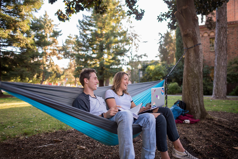 Jared Hatcher (Freshman, Pre nursing, age 19, from Santa Cruz) (left) and Natalie Litvak (Freshman, Undeclared, age 18, from Moorpark) (right) study while sitting in a hammock between two trees on the Kendall Hall lawn on Friday, October 13, 2017 in Chico, Calif.<br /> (Jason Halley/University Photographer)
