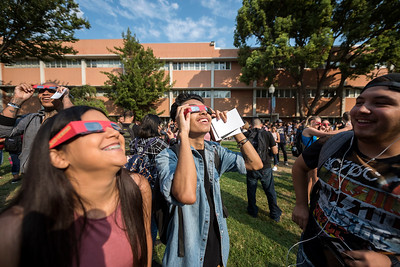 Allyah Perez, 19 (left), Ernesto Gonzalez, 19 (right), and other students experience a partial 83.4% of total solar eclipse on the first day of classes during Chico Del Sol event on Monday, August 21, 2017 in Chico, Calif. (Jason Halley/University Photographer)