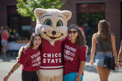 Tiffany Rivas, Willie the Wildcat, Victoria Barnes (left to right), and volunteers help new students move in to their dorm rooms on Thursday, August 17, 2017 in Chico, Calif. (Jason Halley/University Photographer)