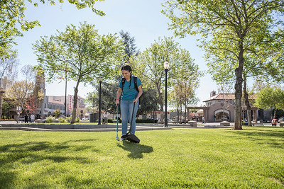Natalie Alva picks up trash in the City Plaza as students spent César Chávez Day giving back through the 'Cats in the Community event, which sends volunteers to local parks and nonprofit organizations to help out on Thursday, March 31, 2016 in Chico, Calif.  (Jason Halley/University Photographer)