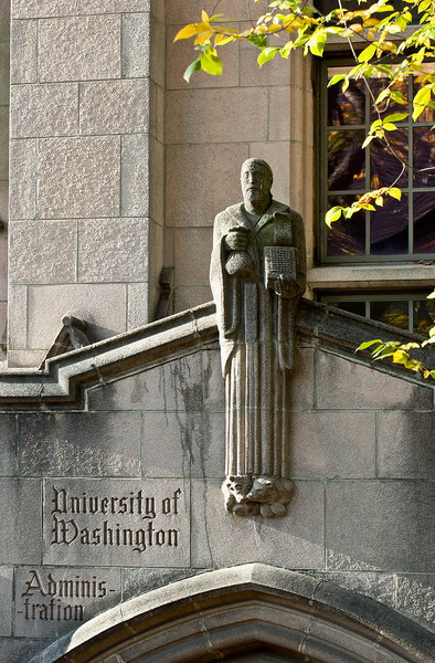 Figure above SE entrance to Gerberding Hall (formerly known as the Administration Building).  Many of the gargoyles and other sculpted figures depict various disciplines within the University.  Some say that this one holding a bag of money in his right hand and a comptometer in his left represents Business Administration but my colleagues in the Foster School of Business deny that it is a fair representation.