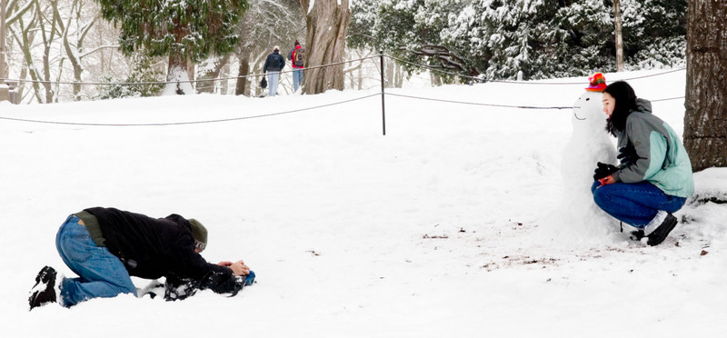 Student photographing his girlfriend with a snowman they had just made. near Denny Hall