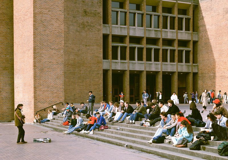 A troubadour entertains students in front of Odegard Library in Red Square