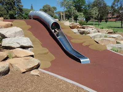 stainless steel tube slide on mound with moulded boulder clambering in softfall rubber