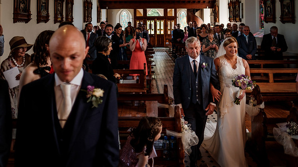 Bride and her father walking down the aisle to her groom