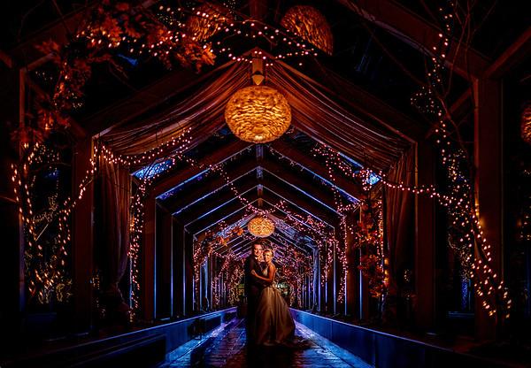 Bride & groom in lit walkway at night