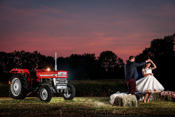Bride and groom twirling near old tractor