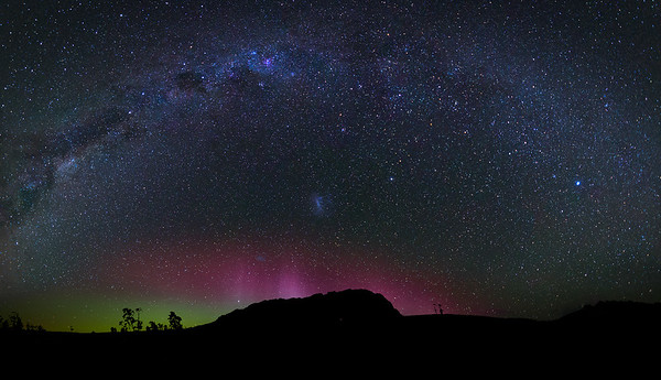 TheAurora Australis dancing behind the silhouette of Mount Roland and with the Milky Way arching above.