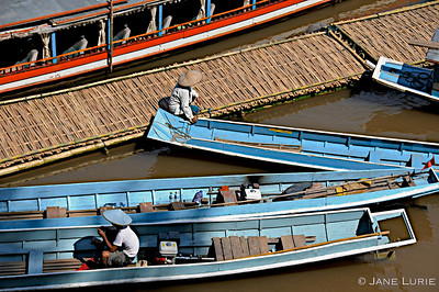 Fishermen taking a break at the dock on their long boats. Mekong River, Laos