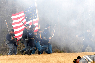 "A group of Union infantry reenactors march across a field littered with ""dead"" bodies. The Skirmish at Gamble's Hotel happened on March 5, 1885 when 500 federal soldiers, under the command of Reuben Williams of the 12th Indiana Infantry, marched into Florence to destroy the railroad depot but were met by Confederate soldiers backed up with 400 militia. The reenactment, held by the 23rd South Carolina Infantry, was held at the Rankin Plantation in Florence, South Carolina on Saturday, March 5, 2011. Photo Copyright 2011 Jason Barnette"