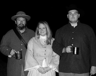 A father and son pose with the son's girlfriend, all wearing period-specific clothing. The Skirmish at Gamble's Hotel happened on March 5, 1885 when 500 federal soldiers, under the command of Reuben Williams of the 12th Indiana Infantry, marched into Florence to destroy the railroad depot but were met by Confederate soldiers backed up with 400 militia. The reenactment, held by the 23rd South Carolina Infantry, was held at the Rankin Plantation in Florence, South Carolina on Saturday, March 5, 2011. Photo Copyright 2011 Jason Barnette