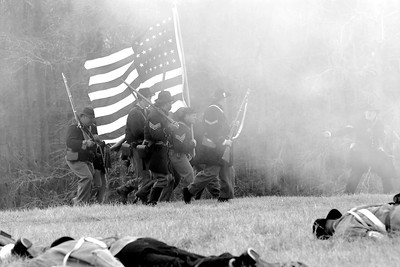 """A group of Union infantry reenactors march across a field littered with """"dead"""" bodies. The Skirmish at Gamble's Hotel happened on March 5, 1885 when 500 federal soldiers, under the command of Reuben Williams of the 12th Indiana Infantry, marched into Florence to destroy the railroad depot but were met by Confederate soldiers backed up with 400 militia. The reenactment, held by the 23rd South Carolina Infantry, was held at the Rankin Plantation in Florence, South Carolina on Saturday, March 5, 2011. Photo Copyright 2011 Jason Barnette"""