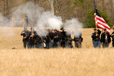 Union infantry reenactors fire at Confederate reenactors across the battlefield. The Skirmish at Gamble's Hotel happened on March 5, 1885 when 500 federal soldiers, under the command of Reuben Williams of the 12th Indiana Infantry, marched into Florence to destroy the railroad depot but were met by Confederate soldiers backed up with 400 militia. The reenactment, held by the 23rd South Carolina Infantry, was held at the Rankin Plantation in Florence, South Carolina on Saturday, March 5, 2011. Photo Copyright 2011 Jason Barnette