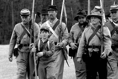 A young boy leads the Confederate infantry reenactors off the battlefield. The Skirmish at Gamble's Hotel happened on March 5, 1885 when 500 federal soldiers, under the command of Reuben Williams of the 12th Indiana Infantry, marched into Florence to destroy the railroad depot but were met by Confederate soldiers backed up with 400 militia. The reenactment, held by the 23rd South Carolina Infantry, was held at the Rankin Plantation in Florence, South Carolina on Saturday, March 5, 2011. Photo Copyright 2011 Jason Barnette