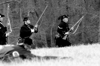 A pair of Union infantry reenactors sprint across the field to capture the last remaining Confederate reenactors, contrary to history. The Skirmish at Gamble's Hotel happened on March 5, 1885 when 500 federal soldiers, under the command of Reuben Williams of the 12th Indiana Infantry, marched into Florence to destroy the railroad depot but were met by Confederate soldiers backed up with 400 militia. The reenactment, held by the 23rd South Carolina Infantry, was held at the Rankin Plantation in Florence, South Carolina on Saturday, March 5, 2011. Photo Copyright 2011 Jason Barnette