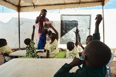 Simon, a volunteer, teaching the alphabet to children at the X-SUBA Learning Center.  They hold classes three days a week (English, Math, and Critical Thinking) during the morning hours.  These classes are designed to keep the children in an educational environment until they can find tuition to attend primary school.