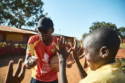 Coach Kenneth instructs students on the proper stance to catch a ball in preparation for a netball game.  Their time with students at local schools starts with a discussion of some sorts, some drills, and then a friendly scrimmage.
