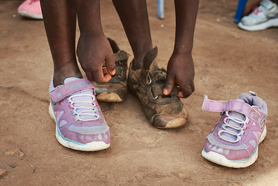 One of X-SUBA's Learning Center students getting a pair of new shoes.  Coach Kenneth brought a few pairs of donated children's shoes from a recent trip to London.