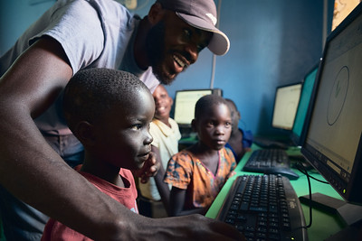 Solomon using a graphics program to teach children how to use a computer mouse.  Computer skills are becoming very important in Uganda, and even children whose parents can't afford school are able to learn these skills at X-SUBA's new ICT center.