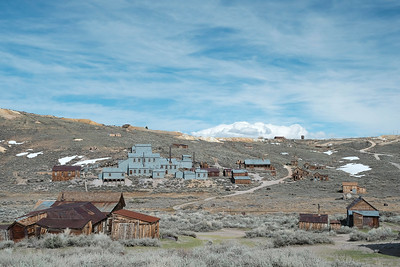 I took a number of town scenes, to try to show the viewer where they're at.  The others just weren't balanced.  This one uses the two buildings on each side of the foreground to frame it, with the winding road leading the eye to the hills.