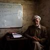 Abdul Satar Moqbal, NRC's education coordinator in Khost, sits in a classroom in the Gulan refugee camp.<br /> <br /> Khost, February 2017<br /> <br /> NRC/Jim Huylebroek