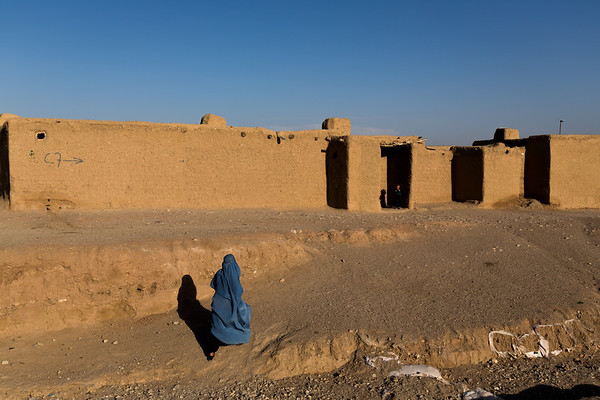 A woman walks home in the Shaedayee settlement for IDPs in Herat, Afghanistan.<br /> <br /> Herat, May 2017<br /> <br /> Photo NRC/Jim Huylebroek