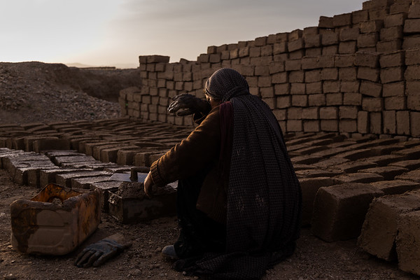 """Khoraman, 41, is a single mother and widow from Du Layna, a district in Afghanistan's central Ghor province. <br /> <br /> Every year the families have to leave. Ghor is impoverished, isolated and largely ungoverned. Militants and criminal gangs wage war against government forces from mountain hideouts. They also fight each other, their loyalties shifting as often as the seasons. Families flee in the middle of the night. Women wrapped in black and purple shawls gather their children and head west to Herat. <br /> <br /> Five years ago, Kheraaman was one such woman. Her husband killed, she fled her mountain home with three children in tow. She is far from alone. More than 50,000 people have been forced to<br /> leave Ghor in the past five years. <br /> <br /> To survive, she makes bricks, 50 to 100 every day, which she sells for a pittance. Because it is piecework, paid by the number of bricks she makes, it is a family effort. An extra pair of hands helps scratch out a meagre wage, even if those hands belong to her child.""""I have two daughters and a son,"""" Khoraman says. """"Since I arrived in Herat I have made thesebricks. Both my daughters and son help me.""""<br /> <br /> Herat, May 2017<br /> <br /> NRC/Jim Huylebroek"""