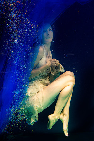 model, half naked under water posing with bubbles and blue fabric