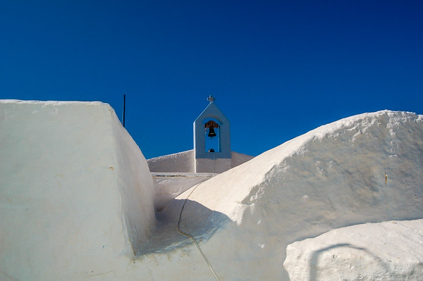 part of a white greek church with blue sky and a little bell