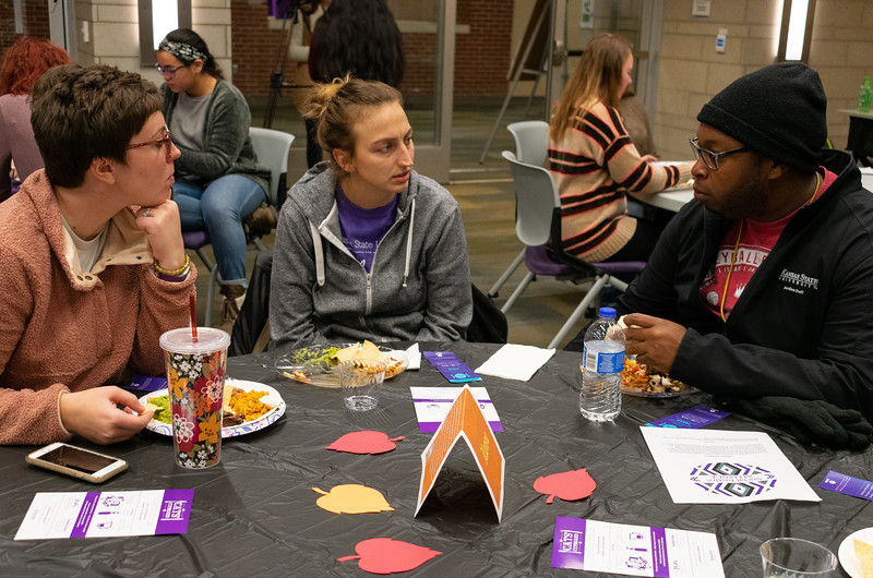 Holly Gerke (left), Mackenzie Lechlitner (middle), and Jerome Kirby (right) socialize during the Unthanksgiving banquet presented by the Department of Housing and Dining Services' Social Justice Alliance. This event took place in the Kramer Tallgrass Ballroom from 5-6:30 p.m. on Nov. 11. (Brooke Barrett | Collegian Media Group)