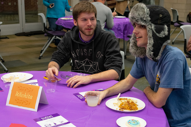 Daniel Wilson (left) and Justin Miller (right) share a meal together at the Unthanksgiving dinner in the Kramer Tallgrass Ballroom on Nov. 11. This event raised awareness to residents about relevant issues in diversity and multiculturalism by celebrating indigenous peoples of America as well as having them participate in a hunger banquet. (Brooke Barrett | Collegian Media Group)