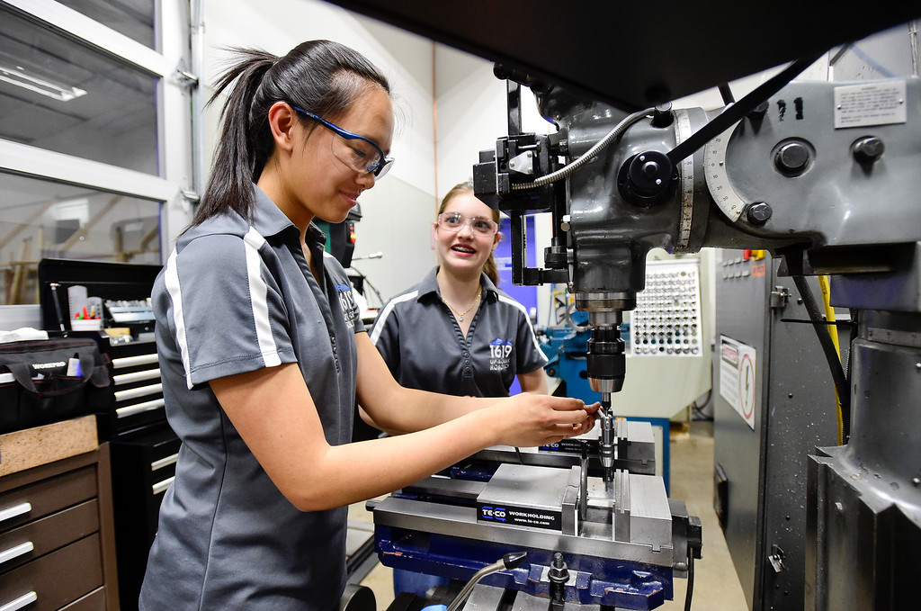 """. Niwot High School Sophomore Esther Xu, left, talks with Silver Creek High School Sophomore Teegan Oatley, right, while working a \""""super secret project\"""" at the Up-A-Creek Robotics practice and engineering facility in Longmont, Colorado on May 8, 2018. (Photo by Matthew Jonas/Staff Photographer)"""
