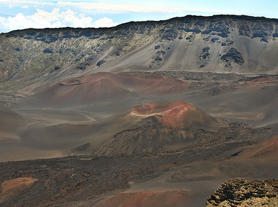 The view (from Kalahaku Overlook) of the western rim of Haleakala's crater and two cinder cones located in the summit basin below the rim. The multicolored ash deposits and darker lava flows mark the most recent volcanic activity with Haleakala's summit basin.