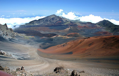 """Haleakala'a Summit Basin (from the Visitor Center) -- Looking down into Pu'u Ula'ula Crater, the cinder cone formed by the last volcanic activity of Haleakala. The different colors of the cinders is caused by oxidation (basically """"rusting"""") of the cinders and other finer-grained materials of the basin. Volcanic """"bombs"""" more than a meter in diameter litter the lower slopes of the basin; these were explosively thrown out of the erupting cinder cone."""