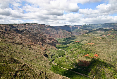 The view upstream in Mokihana Valley, a branch of Waimea Canyon, west Kaua'i. The steep cliffs along the west bank of the Mokihana River (bottom-center portion of photo) are the remains of the west scarp of the Makaweli Graben, a trough-like feature that dropped down between a pair of immense faults associated with the early collapse of the Wai'ale'ale shield volcano the formed Kaua'i.   The long ridge on the horizon (upper-left quadrant of photo) is Kumuwela Ridge, the leading edge of the Olokele Plateau, a remnant of the original slopes of Wai'ale'ale Volcano.