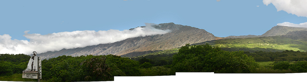 The southern slopes of Haleakala volcano (the rim of the summit basin is visible in the center of the photo, just above the cloud bank) are the awesome backdrop for St. John's Catholic Church near Kaupo on the Pi'ilani Highway, south Maui. This image is a composite of five separate photographs of the ridgeline that forms the volcano's south rim.