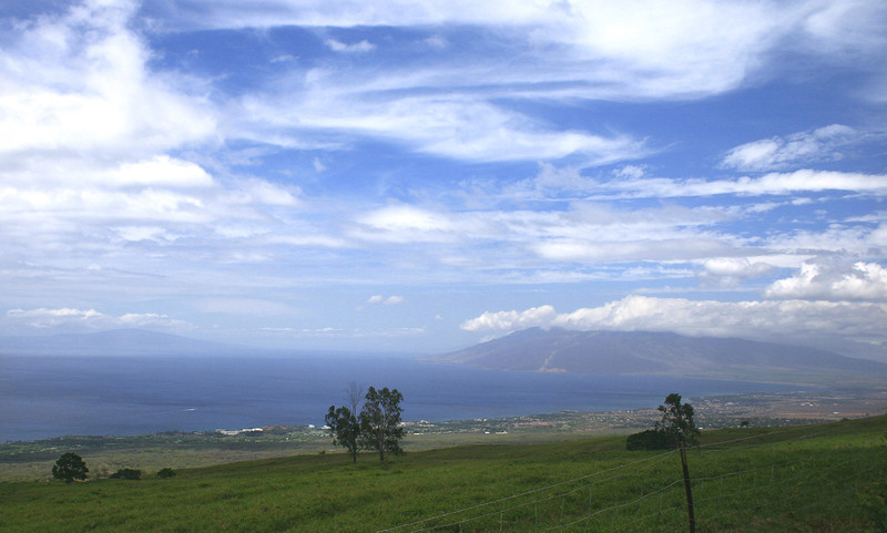 The view of Ma'alaea Bay and the West Maui Mountains (center-left part of frame) from the Pi'ilani Highway just south of Ulupalakua Ranch. The white structures just downslope along the shoreline mark the southernmost extent of the community of Makena, south Maui.