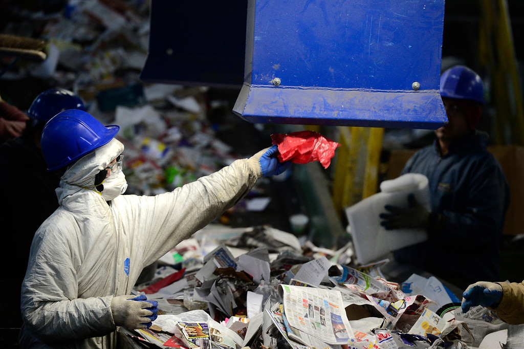 . BOULDER, CO - FEBRUARY 22, 2019 A worker lifts a plastic bag into the new film plastic extraction unit at the Boulder County Recycling Center on Friday February 23, 2019 in Boulder on Friday.  Paul Aiken / Staff Photographer
