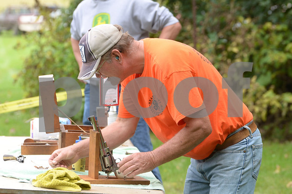 -Messenger photo by Jesse Major<br /> Roger Eichelberger, a Pocahontas County Conservation Board member, loads an old revolver during the Wiegert Prarie Fallfest on Sunday.