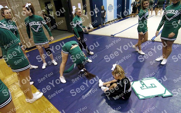 -Messenger photo by Hans Madsen<br /> <br /> Andee Barwin, 6, ties her shoe as members of the St. Edmond High School cheerleading squad prepare for their routine Saturday morning at the Triton Cheerleading Challange held at Iowa Central Community College. Andee is the daughter of the teams coach, Amber Barwin.