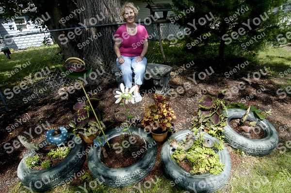 -Messenger photo by Hans Madsen<br /> <br /> Karen Johnson sits behind a set of planters made from painted tires in her backyard garden. He home is the first stop on this year's Fort Dodge Garden Club annual Garden Walk.