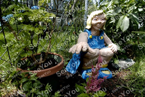 -Messenger photo by Hans Madsen<br /> <br /> A whimsical piece of sculpture by Kris Johnson, Karen Johnson's daughter, helps guard plants along one edge of the yard.