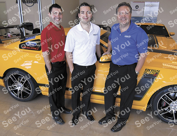 -Messenger photo by Hans Madsen<br /> <br /> From left, Matt, Nick and Casey Johnson pose with a purpose built Ford Mustang racing car in the showroom of Fort Dodge Ford and Toyota.