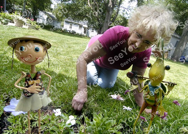 -Messenger photo by Hans Madsen<br /> <br /> Framed by some of the whimsical creaturs found through her garden, Karen  Johnson removes a few errant weeds from one of the flower beds. Her home is the first stop on this year's Fort Dodge Garden Club annual Garden Walk.