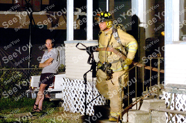 -Messenger photo by Hans Madsen<br /> <br /> Chris Olson watches as a Fort Dodge firefighter emerges from his residence at 116 S. 15th St. around 2:30 a.m. Thursday morning after helping to put out what turned out to be a mop on fire. A previous fire at the home, on July 27, blamed on wiring, damaged a laundry room and back porch.