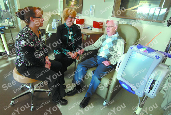 -Messenger photo by Hans Madsen<br /> <br /> Cancer Center RN Natalie Moore, left, along with Trinity Health Systems president and CEO Sue Thompson chat with Gene Nelson in the Infusion Center.