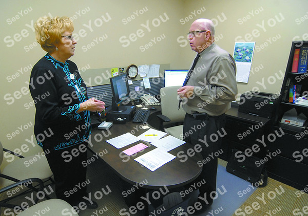 -Messenger photo by Hans Madsen<br /> <br /> Trinity Health Systems president and CEO Sue Thompson stops to visit with Dr. Joe Rhoades at the Trinity Regional Medical Center Cancer Center.