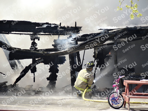 -Messenger photo by Emilie Nelson <br /> <br /> A Fort Dodge firefighter works to put out hotspots in a garage fire at 1621 14th Ave. SW Wednesday afternoon. The Fort Dodge Fire Department responded to the fire, which was likely caused by an unattended woodburner, around 12: 15 p.m. The garage was a total loss.
