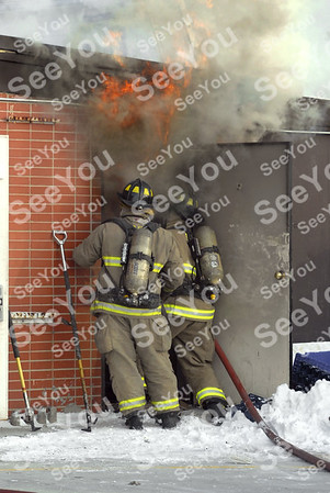 -Messenger photo by Hans Madsen<br /> <br /> Fort Dodge firefighters begin the attact on a fire Thursday afternoon at the New Star Mini Mart located at Fifth Avenue South and South 19th Street.